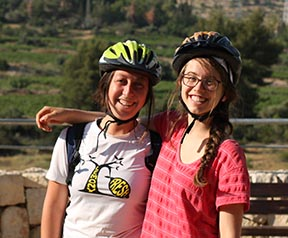 Mimi (on right) and a friend bike riding on the fringes of Jerusalem with the Arava Institute for Environmental studies